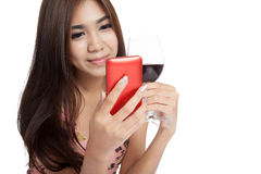 Beautiful Asian woman smile with mobile phone and red wine Stock Photo