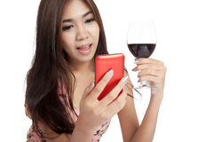 Beautiful Asian woman smile with mobile phone and red wine Royalty Free Stock Photos