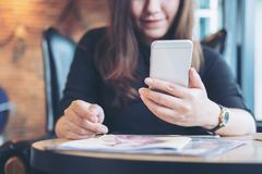A beautiful Asian woman with smiley face holding and using smart phone with magazines. On wooden table in the bistro cafe royalty free stock photos