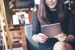 A beautiful Asian woman with smiley face holding and using tablet Royalty Free Stock Photo