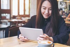 A beautiful Asian woman with smiley face using tablet Royalty Free Stock Photography