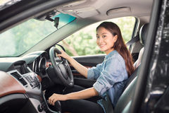 Beautiful Asian woman smiling and enjoying driving a car and han. D is about to drive into gear on road for travel Royalty Free Stock Photography