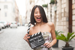 Beautiful asian woman smiling outdoor city street with clapperbo Royalty Free Stock Photos