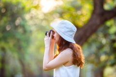 Beautiful asian woman smiling with perfect smile in a park and looking at view screen camera. Selective soft focus Royalty Free Stock Photos