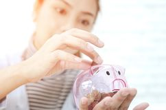 Pink coin jar in Asian women hand. royalty free stock photos