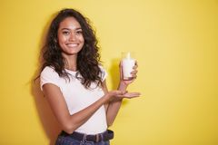 Beautiful asian woman smiling while prresenting a glass of milk. Portrait of beautiful asian woman smiling while prresenting a glass of milk on yellow background Stock Photography