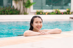 Beautiful asian woman smiling in a swimming pool Stock Photo
