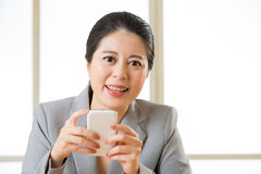 Beautiful Asian woman smiling and using smart phone text messagi Royalty Free Stock Photos