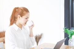 Asian women wearing a white shirt is working and sipping coffee. royalty free stock image