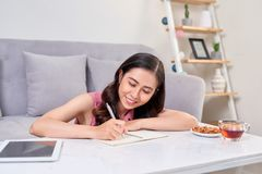 Beautiful Asian woman smiling and writing a notebook on table royalty free stock images