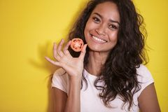 Beautiful asian woman smilingwith slices of tomato. Close up portrait of beautiful asian woman smilingwith slices of tomato on yellow background Stock Images