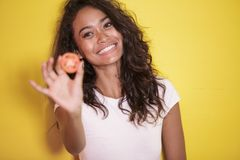Beautiful asian woman smilingwith slices of tomato. Close up portrait of beautiful asian woman smilingwith slices of tomato on yellow background Royalty Free Stock Photography