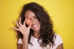 Beautiful asian woman smilingwith slices of tomato. Close up portrait of beautiful asian woman smilingwith slices of tomato on yellow background Royalty Free Stock Image