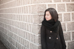 Beautiful asian woman standing by a stone wall Royalty Free Stock Image
