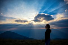 A beautiful asian woman standing and watching sunset with mountains view stock photo