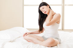 Beautiful asian woman suffering Shoulder neck ache pain tired. Beautiful asian woman suffering Shoulder neck ache tired sit on bed. bedroom background Stock Images