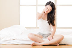 Beautiful asian woman suffering Shoulder neck ache tired. Sit on bed. bedroom background Stock Image