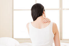 Beautiful asian woman suffering Shoulder neck ache tired. Sit on bed. bedroom background. back view Royalty Free Stock Photos