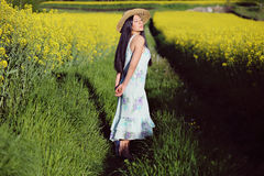 Beautiful asian woman in summer flowered field Royalty Free Stock Image