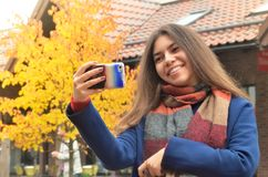 Beautiful Asian woman take a selfie. Beautiful young Asian woman take a selfie against the backdrop of buildings and autumn landscape, holds the phone in hand Royalty Free Stock Photo