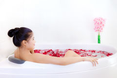 Beautiful asian woman takes a bath in jacuzzi with rose petals Royalty Free Stock Photos