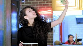 Beautiful asian woman taking selfies on a smartphone. Young asian girl take photo with pho soup at cafe shop. Chinese. Vietnamese or Japanese cafe or stock video footage