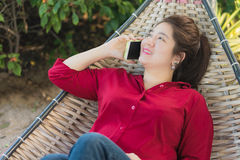 Beautiful Asian woman is talking on mobile phone Stock Image