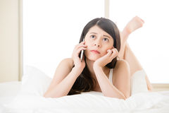 Beautiful asian woman talking on smart phone in bedroom Royalty Free Stock Images