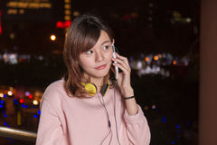 Beautiful Asian woman talking on smart phone and yellow headphon Royalty Free Stock Photos