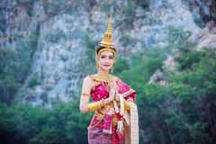 Beautiful woman holding flower and smiles. Beautiful asian woman in Thai traditional dress holding flower and smiles royalty free stock photography