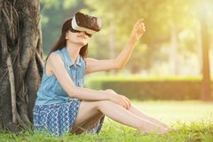 Beautiful asian woman touch screen with VR headset. Beautiful asian woman touch screen with virtual reality sitting on grass in outdoor park. VR headset glasses Royalty Free Stock Photos