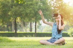 Beautiful asian woman touch scrrn with VR headset. Beautiful asian woman touch screen with virtual reality sitting on grass in outdoor park. VR headset glasses Royalty Free Stock Photography