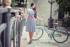 Beautiful asian woman travel at asia by city vintage bicycle. At summer time, she is dressed in elegant dress and standing on bridge Stock Image