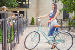 Beautiful asian woman travel at asia by city vintage bicycle. At summer time, she is dressed in elegant dress and standing on bridge Stock Photo