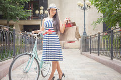 Beautiful asian woman travel by city vintage bicycle. She is dressed in elegant dress and standing on bridge Royalty Free Stock Photo