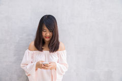 Beautiful asian woman using cellphone on concrete wall Royalty Free Stock Images