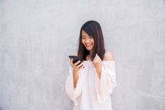Beautiful asian woman using cellphone over concrete wall Royalty Free Stock Photos