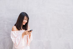 Beautiful asian woman using cellphone over on concrete wall Royalty Free Stock Images