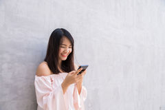 Beautiful asian woman using cellphone, over concrete wall Stock Photography