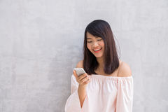Beautiful asian woman using cellphone the over concrete wall Stock Image
