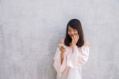 Beautiful asian woman using cellphone, over concrete wall Royalty Free Stock Image