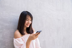 Beautiful asian woman using cellphone over concrete wall Stock Photography
