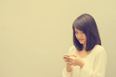 Beautiful asian woman using cellphone, over concrete wall. Stock Images