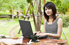Beautiful Asian woman using computer notebook. Royalty Free Stock Images
