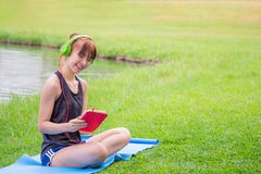 Beautiful asian woman using headphones listening music with smart phone or tablet on grass in outdoor park. nature outdoors backg stock photography