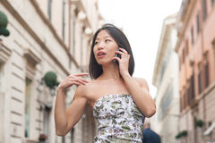 Beautiful asian woman using mobile phone spring urban outdoor Royalty Free Stock Photography