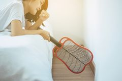 Beautiful asian woman using mosquito swatter at house,Female with mosquito electric net racket in bedroom royalty free stock images