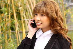 Beautiful asian woman using smart phone. In the park Royalty Free Stock Photo