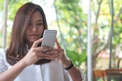 Asian woman using smart phone with feeling relax in modern cafe. A beautiful Asian woman using smart phone with feeling relax in modern cafe Stock Photos