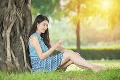 Beautiful asian woman using smart phone in outdoor. Beautiful asian woman using smart phone sitting on grass in outdoor park. nature outdoors background. people Stock Photo